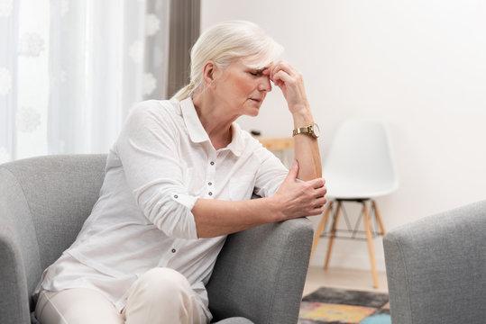 Older woman has a headache.