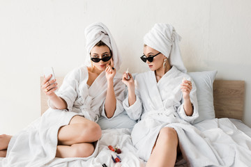 stylish women in bathrobes and sunglasses, towels and jewelry doing pedicure and taking selfie in bed