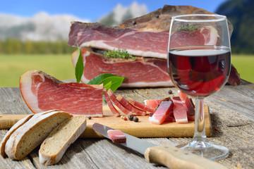 Südtiroler Speckjause mit Vinschgerl und einem Glas Rotwein vor einer Berglandschaft in den Alpen – South Tyrolean bacon snack with local rye bread and a glass od red wine in front of mountains of the