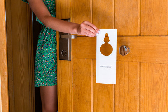 female hand hangs a sign on the door do not disturb in hotel