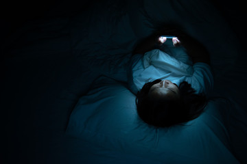 Asian woman playing game on smartphone in the bed at night,Thailand people,Addict social media