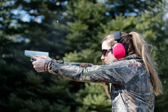 A woman shooting a handgun and the ejected cartridge case in the air.