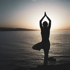 Beauty girl on beach in yoga pose, asana silhouette
