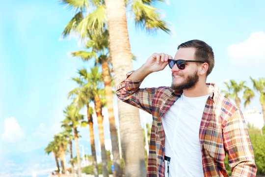 Bearded hipster guy wearing vintage plaid checkered shirt at tropical destination. Portrait of young man in white t-shirt smiling over exotic background. Copy space, close up.