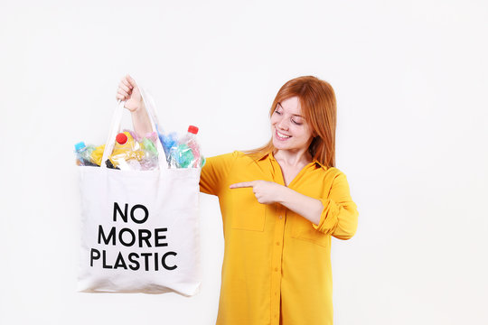 Emotional redhead woman holding eco friendly shopping bag with no more plastic text, full of harmful products, bottles and bags. Zero waste concept. Happy female sorting, separating garabage.