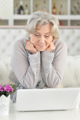 Portrait of senior woman using laptop while sitting on sofa