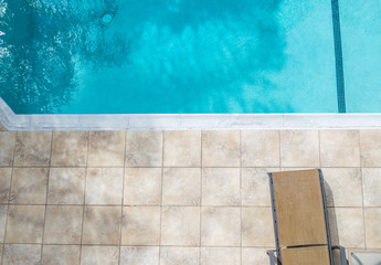 empty lounger chair on a tile pool deck next to a clear blue swimming pool with copy space Wall mural