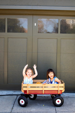 Two young girl playing inside of a red wagon outside on a sunny day.