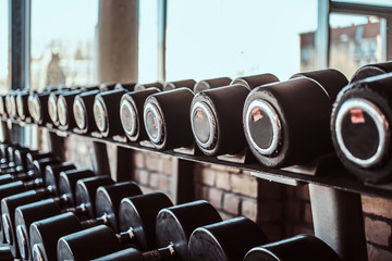 Keuken foto achterwand Fitness Photo of many different dumbbells in modern sunny gym.