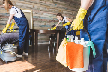Obraz Cleaning service with professional equipment during work. professional kitchenette cleaning, sofa dry cleaning, window and floor washing. man and women in uniform, overalls and rubber gloves - fototapety do salonu