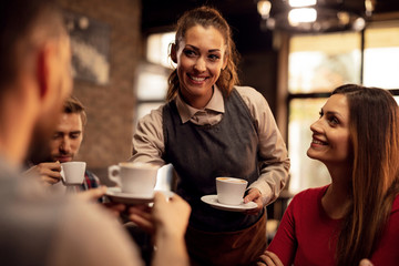 Happy waitress serving coffee to her guest in a cafe, Wall mural