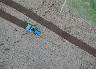 small tractor ploughing in the field. aerial view, agriculture