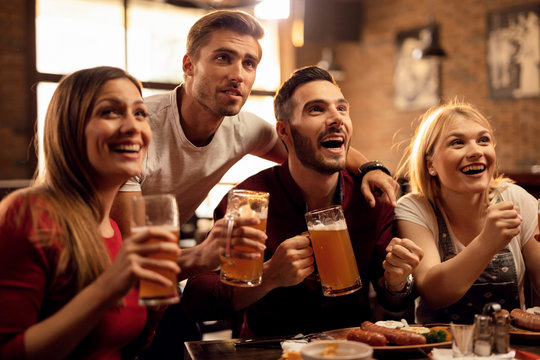 Group of happy young people drinking beer and watching sports match in a pub.