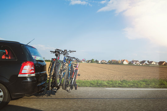 View from the highway over the plowed land and fast Opel car carrying four bikes