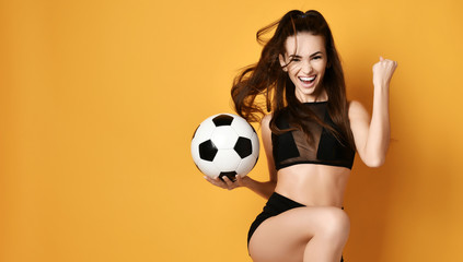 Sporty woman player or fan in black uniform with the soccer ball celebrates happily a win and gesticulate actively