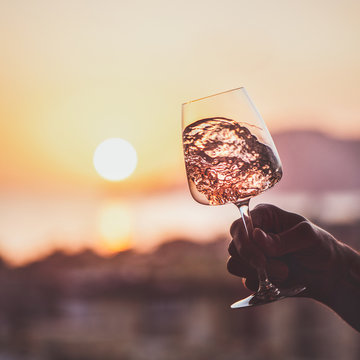 Glass of rose wine in mans hand with sea and sunset at background, close-up, square crop. Summer evening relaxed mood concept