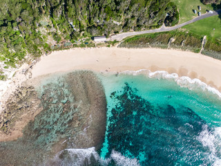 Stunning aerial drone view of Ned's Beach on Lord Howe Island in the Tasman Sea. Beautiful white sand beach, turquoise water, waves and corals. Lord Howe belongs to New South Wales, Australia.