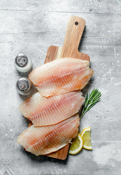 Fish fillet on a wooden cutting Board with rosemary, spices and lemon slices.