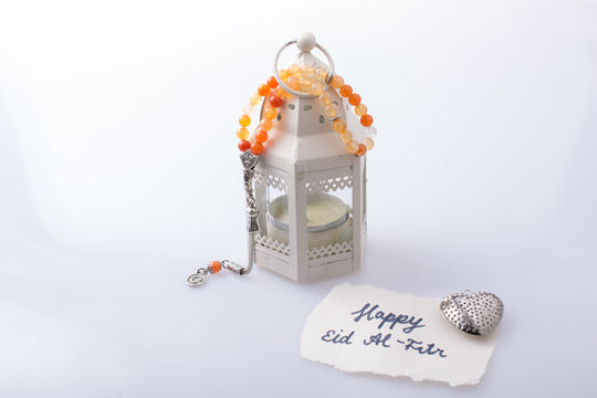 the word EID EL FITR   on torn paper beside lantern and prying beads