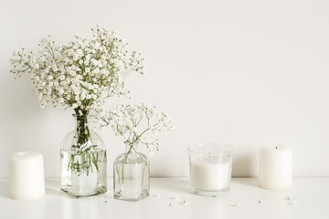 White arrangement of baby's breath flowers and candles. Copy space for lettering