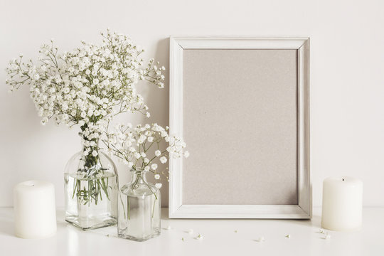 Candles, gypsophila flowers and photo frame on table wall background. Front view mockup
