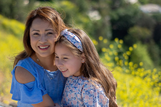 Latina Mother and Daughter Smiling and laughing on a hill in front of yellow flowers