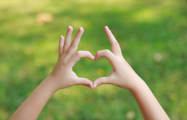Child hands with heart sign on blur green lawn background. Wall mural