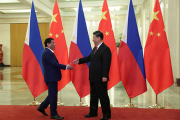 Philippine President Rodrigo Duterte shakes hands with Chinese President Xi Jinping before their meeting at the Great Hall of People in Beijing