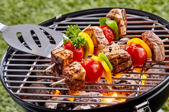 Grilling colorful kebabs over a portable barbecue
