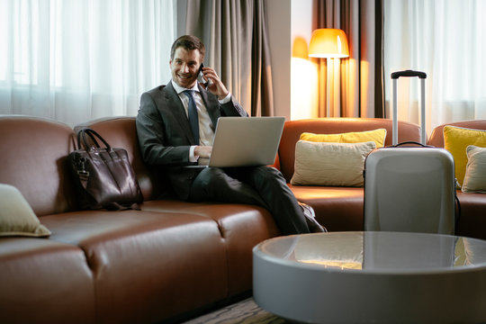 Man at the hotel working on his laptop, has phone call. Executive manager talking on the phone while working on his laptop. Businessman sitting on the hotel sofa working.