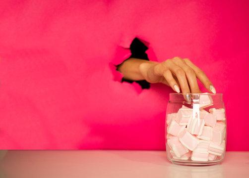 a hand steals a marshmallow