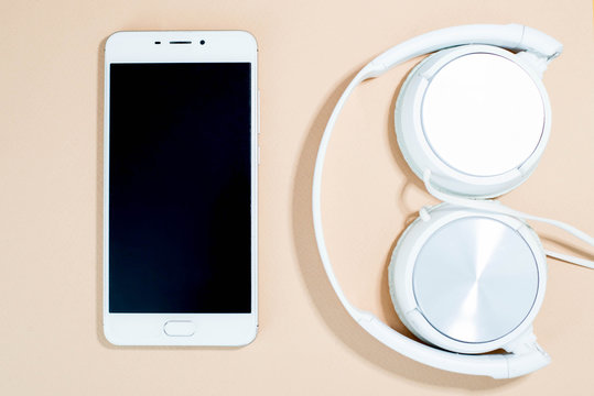 White smartphone with headphones on pink background