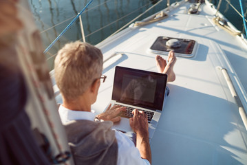 Senior man is working during the vacation on a sailboat