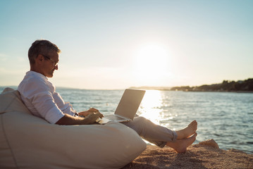 Senior man working on his laptop lying on deck chair on the beach during sunset Fototapete