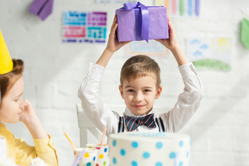 selective focus of boy holding present and looking at camera during birthday party