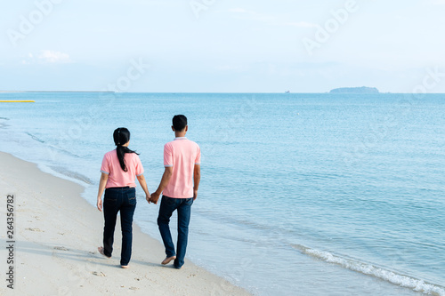 Couples Walking On The Beach On A Summer Vacation Stock Photo And