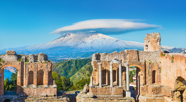 Ancient Greek theatre in Taormina on background of Etna Volcano, Sicily, Italy.
