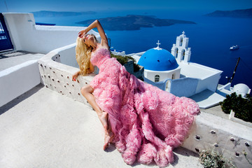 Beautiful woman, bride in an elegant wedding dress, stands against the background of a luxury Santorini Island