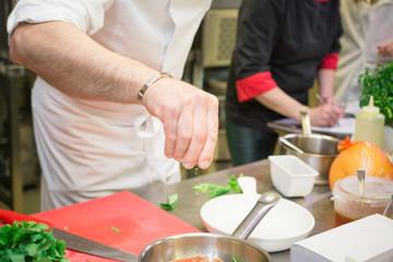 Keuken foto achterwand Koken Closeup mid section of a chef putting salt