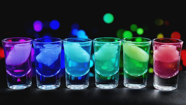 Variation of hard alcoholic shots with ice served on bar counter. Blur neon background