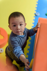 Asian baby boy in indoor playground