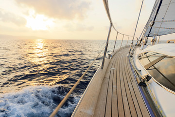 Yacht sailing towards the sunset Wall mural