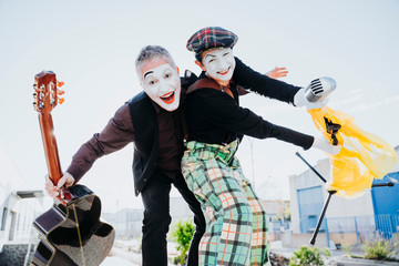 Two mimes on the street singing and playing guitar