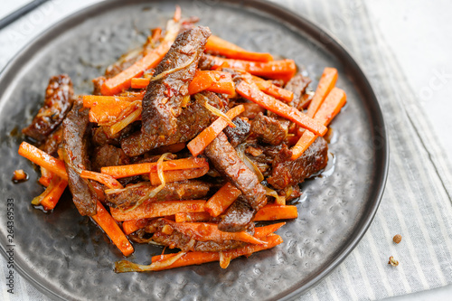Close-up of Chinese spicy Szechuan beef meal on a black plate with