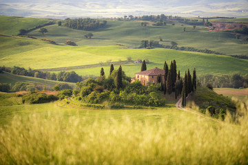 Foto op Canvas Meloen Country farm among grass hills in Tuscany, rural landscape. Countryside farm, cypresses trees, green field,Italy, Europe.