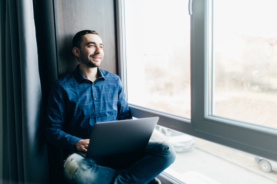 Handsome man working on a windowsill with a laptop. Worker communicating on the Internet. Funny man play for laptop
