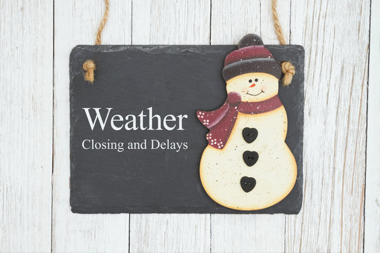 Weather closing and delays sign on a hanging chalkboard with snowman