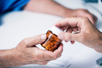 doctor giving a bottle of pills to a senior man