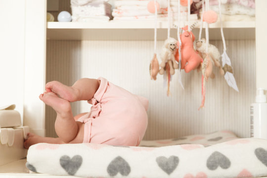 Baby girl lying on the changing table