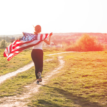 Happy women running in the field with American flag USA celebrate 4th of July
